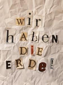 Wir haben die Erde - Kresse-Wallner 2009: Foto einer Illustration auf zerknittertem Papier. Ausgeschnittene Buchstaben aus Zeitungen zeigen den Text: WIR HABEN DIE ERDE!